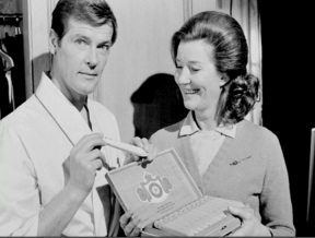 live_and_let_die_lois_maxwell_presents_roger_moore_with_a_cigar_on-set