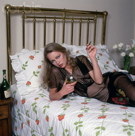 michelle_phillips_reclining_on_bed_with_wine