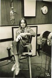 michelle_phillips_sitting_in_high_chair_in_recording_studio