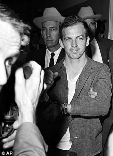 john_f_kennedy_assassination_lee_harvey_oswald_shot_showing_he's_handcuffed_to_phhotographers_november_23_1963
