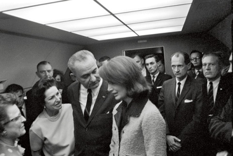 john_f_kennedy_assassination_moments_after_lyndon_b_johnson_is_sworn_in_as_new_president_aboard_air_force_one_new_first_lady_lady-bird_johnson_tells_her_'a_nation_mourns'_with_her