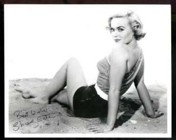 shirley_eaton_sitting_on_sand_looking_over_shoulder