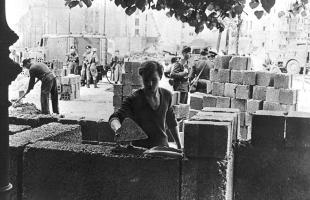 berlin_wall_1961_an_east_german_worker_lays_bricks_as_he_builds_the_walls