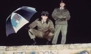 berlin_wall_1989_a_guard_on_the_wall_holds_an_MTV_umbrella_shortly_before_the_wall_falls