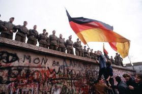 berlin_wall_1989_a_west_german_waves_a_giant_german_flag_in_defiance_of_east_german_guards