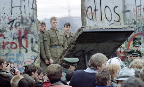 berlin_wall_1989_east_german_guards_look_on_as_a_chunk_of_the_wall_comes_down