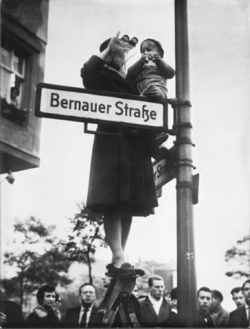 berlin_wall_a_woman_and_a_child_wave_across_the_wall