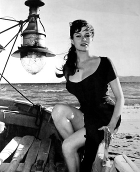 luciana_paluzzi_posing_on_boat_with_lamp_on_beach